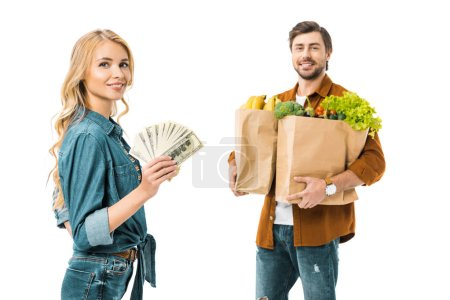 young positive woman showing money while her boyfriend standing behind with products in shopping bags isolated on white