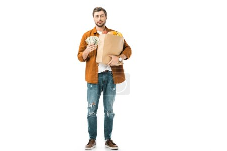 young man showing cash money and holding paper bag full of products isolated on white