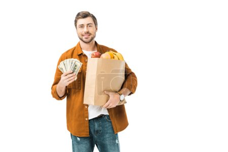 happy man showing cash money and holding paper bag full of products isolated on white
