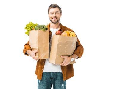 Photo pour Gai homme tenant des sacs en papier remplis de produits isolés sur blanc - image libre de droit