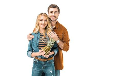 Photo pour L'homme embrassant copine heureuse alors qu'elle tenue d'ananas isolé sur blanc - image libre de droit