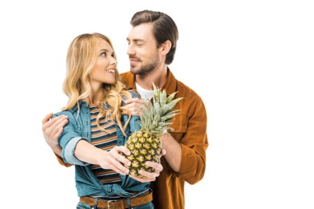 handsome man embracing girlfriend while she showing pineapple isolated on white