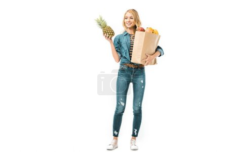 smiling young woman looking at pineapple and holding paper bag with products isolated on white