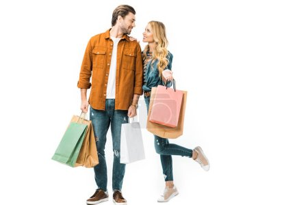 Photo pour Couple tenant des sacs à provisions colorés et se regardant isolés sur blanc - image libre de droit