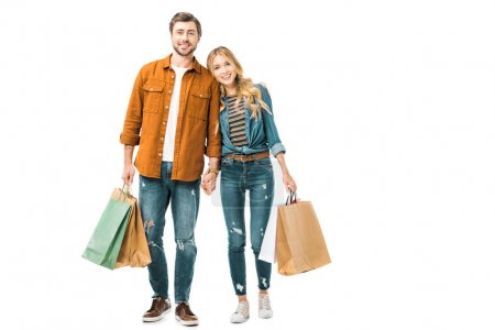 cheerful couple holding colorful shopping bags isolated on white
