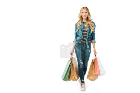 Photo for Attractive stylish young woman walking with colorful shopping bags isolated on white - Royalty Free Image