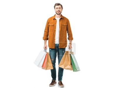positive young man holding colorful shopping bags isolated on white