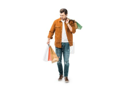 young man walking with colorful shopping bags isolated on white