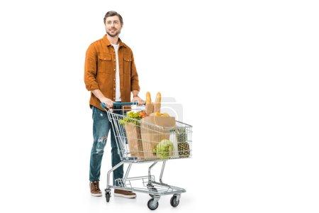 gai homme portant caddie avec les produits de sacs en papier isolés sur blanc