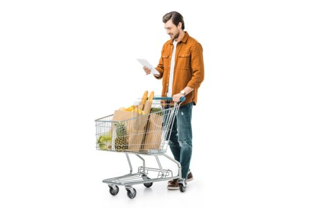 handsome man checking shopping list on digital tablet and carrying shopping trolley isolated on white