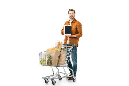 happy man showing digital tablet with blank screen near shopping trolley with paper bags isolated on white