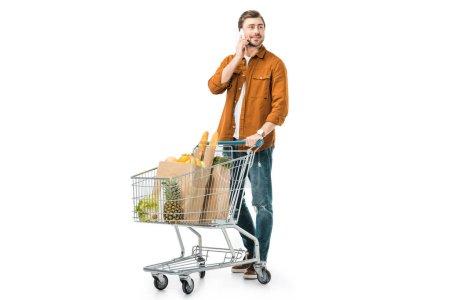Foto de Hombre alegre llevando carrito de la compra con productos en bolsas de papel y hablando por teléfono inteligente aislado en blanco - Imagen libre de derechos