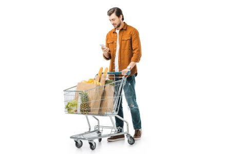 happy handsome man carrying shopping trolley with products in paper bags and using smartphone isolated on white
