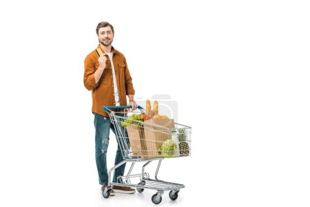 man showing credit card while standing near shopping cart with paper bags isolated on white