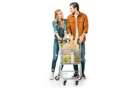 Foto de Pareja feliz llevando el carrito de la compra con productos y mirando el uno al otro aislado en blanco - Imagen libre de derechos