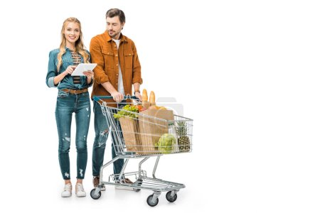 young woman checking shopping list on digital tablet while her boyfriend standing near with trolley full of paper bags with products isolated on white