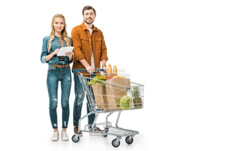 happy girl checking shopping list on digital tablet while her boyfriend standing near with trolley full of paper bags with products isolated on white