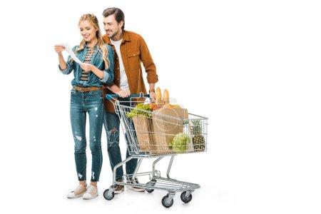 Foto de Feliz pareja con carro lleno de productos en bolsas de papel en compras cheque aislado en blanco - Imagen libre de derechos