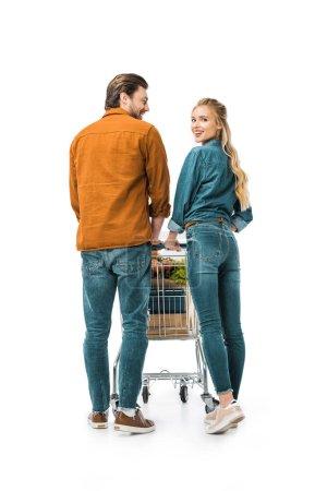 jolie fille heureuse en regardant la caméra tandis que son petit ami transportant le caddie avec les sacs en papier isolés sur blanc