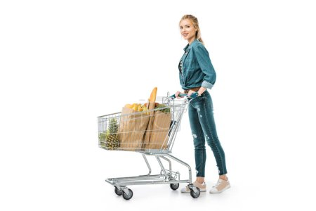 cheerful young woman carrying shopping trolley with products isolated on white