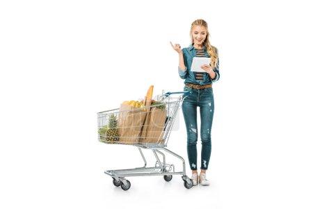 Foto de Sonriente mujer joven con tableta digital haciendo gesto de idea y de pie junto a la carretilla de las compras con los productos aislados en blanco - Imagen libre de derechos