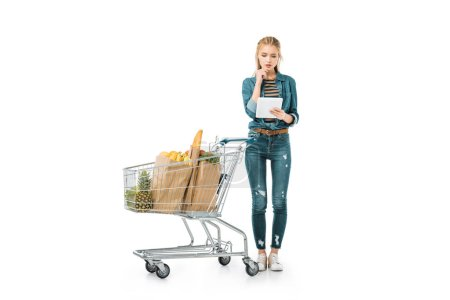 thoughtful woman looking at digital tablet and standing near shopping trolley with products isolated on white