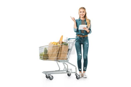 attractive young woman with digital tablet doing idea gesture and standing near shopping trolley with products isolated on white
