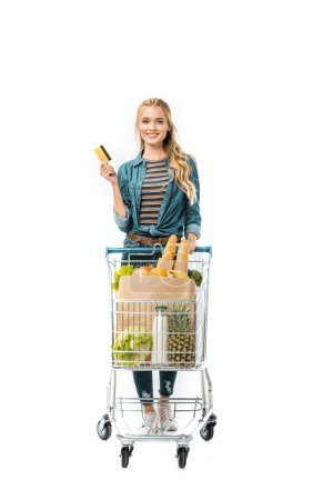 cheerful woman showing credit card and carrying shopping trolley with products isolated on white