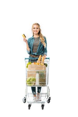 Foto de Mujer alegre, mostrando la tarjeta de crédito y llevar el carrito de la compra con productos aislados en blanco - Imagen libre de derechos