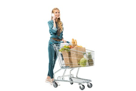 attractive girl talking on smartphone and carrying shopping trolley with products isolated on white