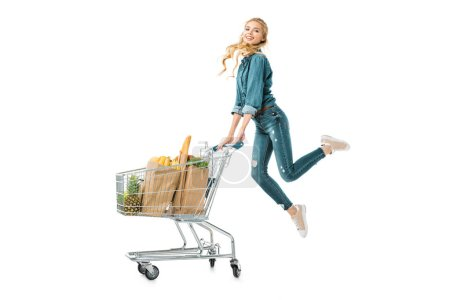 positive beautiful girl jumping near shopping trolley cart with products in paper bags isolated on white