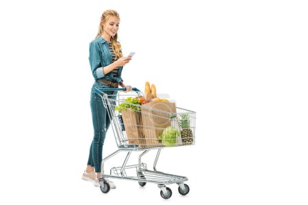 Photo for Smiling woman using smartphone and carrying shopping trolley with products isolated on white - Royalty Free Image
