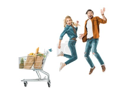happy young couple jumping near shopping trolley full of products in paper bags isolated on white