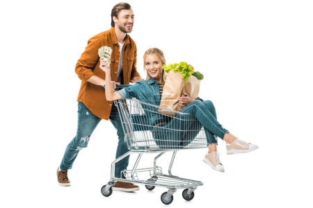 handsome man carrying shopping trolley with happy girlfriend showing money and holding paper bags with products isolated on white
