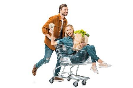 Photo pour Homme portant le caddie avec bonne copine montrant l'argent et la tenue des sacs en papier avec produits isolés sur blanc - image libre de droit