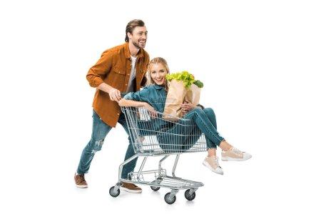 Photo pour Positive homme portant chariot avec copine heureuse holding sacs à provisions avec produits isolés sur blanc - image libre de droit
