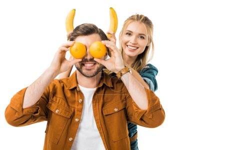 smiling young woman doing horns with bananas to boyfriend while he covering eyes by oranges isolated on white