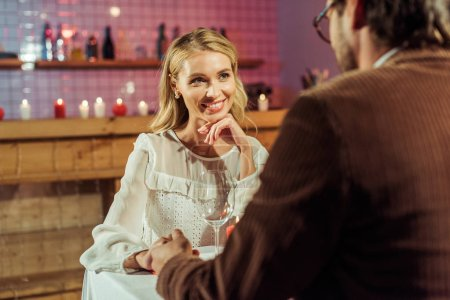 attractive happy woman having date and holding hands with boyfriend at restaurant