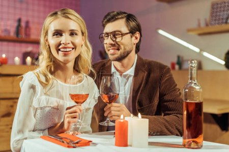 laughing couple with wine glasses celebrating and having date at table with candles in restaurant
