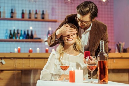 Photo pour Homme en veste tenant boîte cadeau avec anneau et couvrant les yeux de la petite amie pendant le dîner romantique au restaurant - image libre de droit