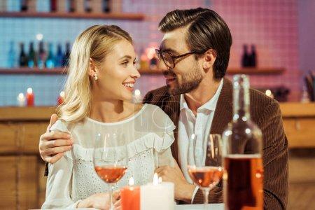 homme gai dans lunettes et copine embrassant veste à table avec des bougies dans le restaurant