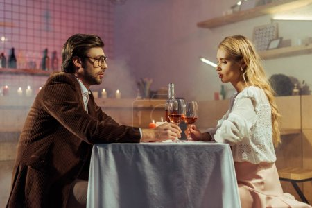 side view of couple having romantic dinner at table with candles and wine glasses in restaurant