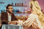 selective focus of couple holding hands and having romantic dinner at table with candles and wine glasses in restaurant