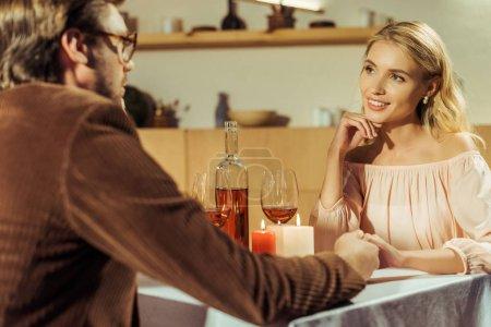 Photo pour Vue partielle de l'homme tenant la main avec une belle petite amie pendant la date dans le café - image libre de droit