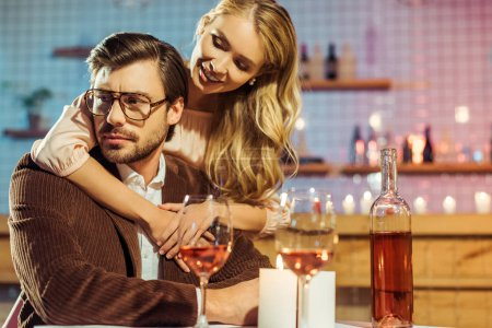 beautiful young woman embracing upset boyfriend during romantic dinner at table in restaurant