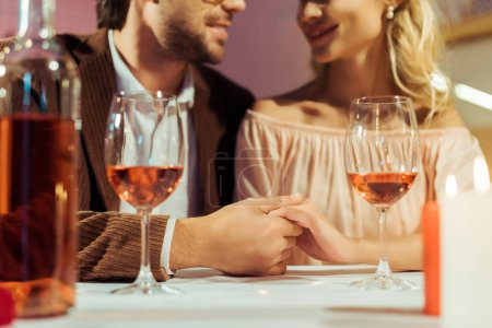 cropped image of couple holding hands and having date at table with wine glasses in restaurant