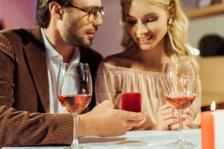 partial view of man proposing to girlfriend at table with wine glasses in restaurant