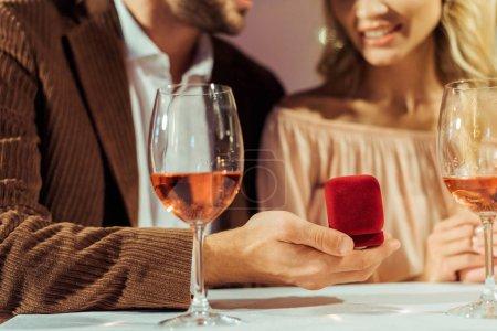 Photo pour Image recadrée de l'homme proposant à sa petite amie lors d'un dîner romantique au restaurant - image libre de droit