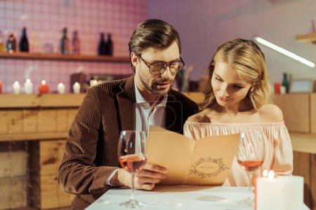 Photo for Couple looking at menu during romantic dinner in restaurant - Royalty Free Image