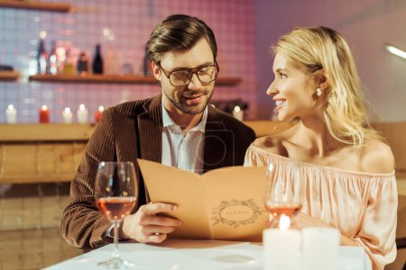 happy young couple looking at menu during romantic dinner in restaurant